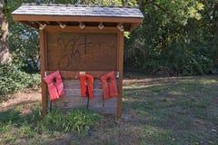 Tre giubbotti di salvataggio arancio che passano su una parete marrone fotografia stock
