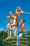 Tre gladlynta barn på stång på lekplatsen Arkivbilder