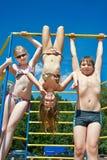 Tre gladlynta barn på stång på lekplatsen Royaltyfri Foto
