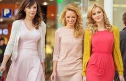 Tre gladlynta kvinnor i shoppinggallerian Royaltyfri Bild