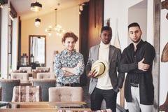 Tre gladlynta unga män som tillsammans står och ler arkivfoto