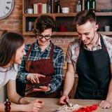 Tre gladlynta vänner tycker om tid som lagar mat tillsammans mål på kupolen arkivfoton