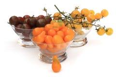 Tre glass bunkar fyllde med körsbärsröda tomater tre olika typer Arkivfoto