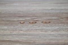 Tre gocce di acqua su fondo di legno Fotografia Stock