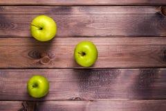 Tre gröna äpplen på tabellen Arkivfoto