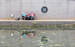 Tre grabbar som pratar nära kanalen fotografering för bildbyråer
