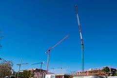 Tre grandi alte gru nell'ambito di una nuova costruzione Fotografie Stock Libere da Diritti