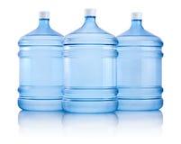 Tre grandi bottiglie di acqua isolate su fondo bianco Fotografia Stock