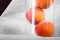 Tre grandi ed intere pesche in un vetro trasparente su un fondo leggero del tessuto Pesche appetitose in pieno delle vitamine nut Fotografia Stock