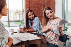 Tre groupmates femminili che preparano per la lettura dell'esame parla le note che si siedono alla tavola in una stanza Fotografia Stock