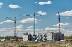 Tre gru nella costruzione di nuovo edificio dell'appartamento Immagine Stock