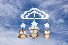 Tre gufi del feltro sul cellulare della culla di bambino contro il cielo nuvoloso Fotografia Stock