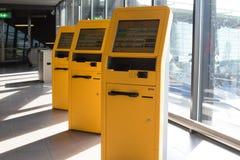 Tre gula flygplatsincheckningportaler på den schiphol flygplatsen fotografering för bildbyråer