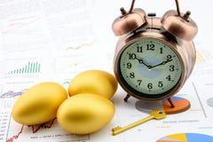 Tre guld- ägg och en guld- tangent med en klocka på affär och finansiella rapporter Royaltyfri Bild