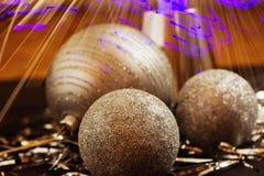Tre guld- jul klumpa ihop sig på backgound för den guld- tråden, ljus stråle Arkivbild