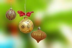 Tre guld- julstruntsaker Royaltyfri Bild