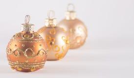 Tre guld- julstruntsaker Arkivfoton