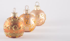 Tre guld- julstruntsaker Royaltyfria Bilder