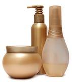 Tre guld- plast-krus och flaskor som isoleras på Arkivbilder