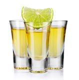 Tre guld- tequilaskott med limefrukt som isoleras på vit fotografering för bildbyråer