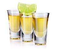 Tre guld- tequilaskott med limefrukt som isoleras på vit arkivbilder