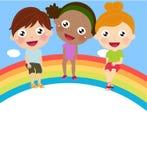 Tre gulliga barn som sitter på regnbågen Arkivfoton
