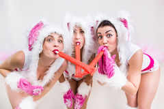 Tre gulliga flickor i en kaninvit och rosa färg kostymerar att blåsa i röret Arkivfoton