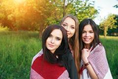 Tre gulliga flickor som utomhus står i plädet, bästa vän som har roligt och in skrattar, parkerar arkivbild