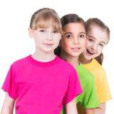 Tre gulliga lilla gulliga le flickor i färgrika t-skjortor Royaltyfri Foto
