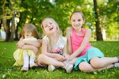 Tre gulliga lilla systrar som har gyckel tillsammans på gräset på en solig sommardag Roliga ungar som tillsammans utomhus hänger Arkivbilder