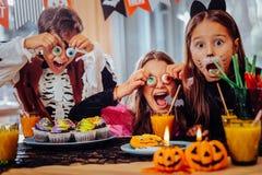 Tre gulliga skolbarn som spelar trick, medan ha allhelgonaaftonpartiet med sötsaker fotografering för bildbyråer