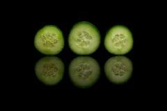 Tre gurkor på svart reflekterande bakgrund Royaltyfria Foton