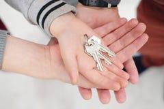 Tre händer, kvinnor, män och barn, viks tillsammans, rymmer tangenterna till den nya lägenheten arkivbild