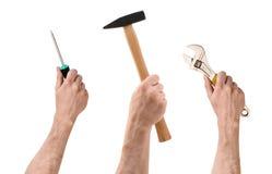 Tre händer med skruvmejsel, hammaren och skiftnyckeln på vit bakgrund Arkivfoton