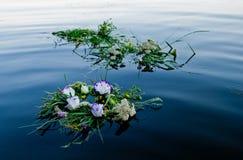 Tre härliga buketter en krans av blommor som svävar längs flodstillhetvattnet av Ivan Kupala royaltyfri bild