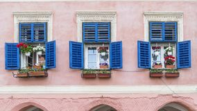 Tre härliga fönster uppställda i en slott i den historiska mitten av Sibiu, Transylvania, Rumänien arkivbilder