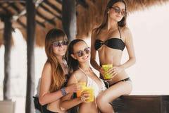 Tre härliga flickor i en stång på stranden Royaltyfria Bilder