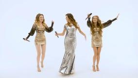 Tre härliga flickor i skinande klänningar flyttar sig plasticly och sjunger arkivfilmer