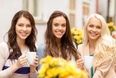Tre härliga flickor som dricker kaffe i kafé Fotografering för Bildbyråer