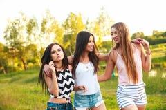 Tre härliga flickor som går och skrattar på solnedgång i parkera stående två för pelikan för kamratskap för bakgrundsbegrepp våt  fotografering för bildbyråer