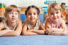 Tre härliga flickor som ligger på golv Fotografering för Bildbyråer
