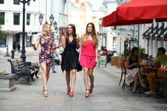 Tre härliga flickvänner för unga kvinnor går på en sommargata fotografering för bildbyråer