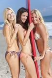Tre härliga kvinnasurfarear med surfingbrädan arkivfoto