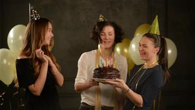 Tre härliga kvinnor i roliga lock på partiet Ett av dem hållande chokladkaka Födelsedagflicka med kort lockigt lager videofilmer