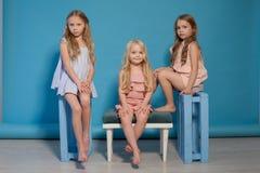 Tre härliga liten flickaklänningar danar ståendesystrar royaltyfri foto