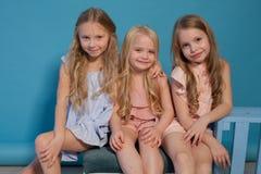 Tre härliga liten flickaklänningar danar ståendesystrar royaltyfria bilder