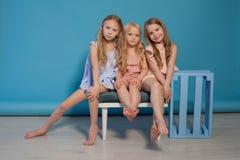 Tre härliga liten flickaklänningar danar ståendesystrar royaltyfria foton