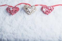 Tre härliga romantiska tappninghjärtor hänger på en röd musikband på en vit snöbakgrund Begrepp för förälskelse- och St-valentind Royaltyfri Bild