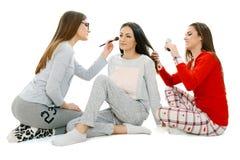 Tre härliga unga flickor har gyckel på sleepover arkivbilder