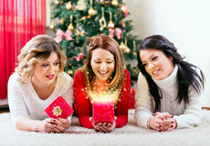Tre härliga unga kvinnor som öppnar en julklapp Royaltyfri Fotografi